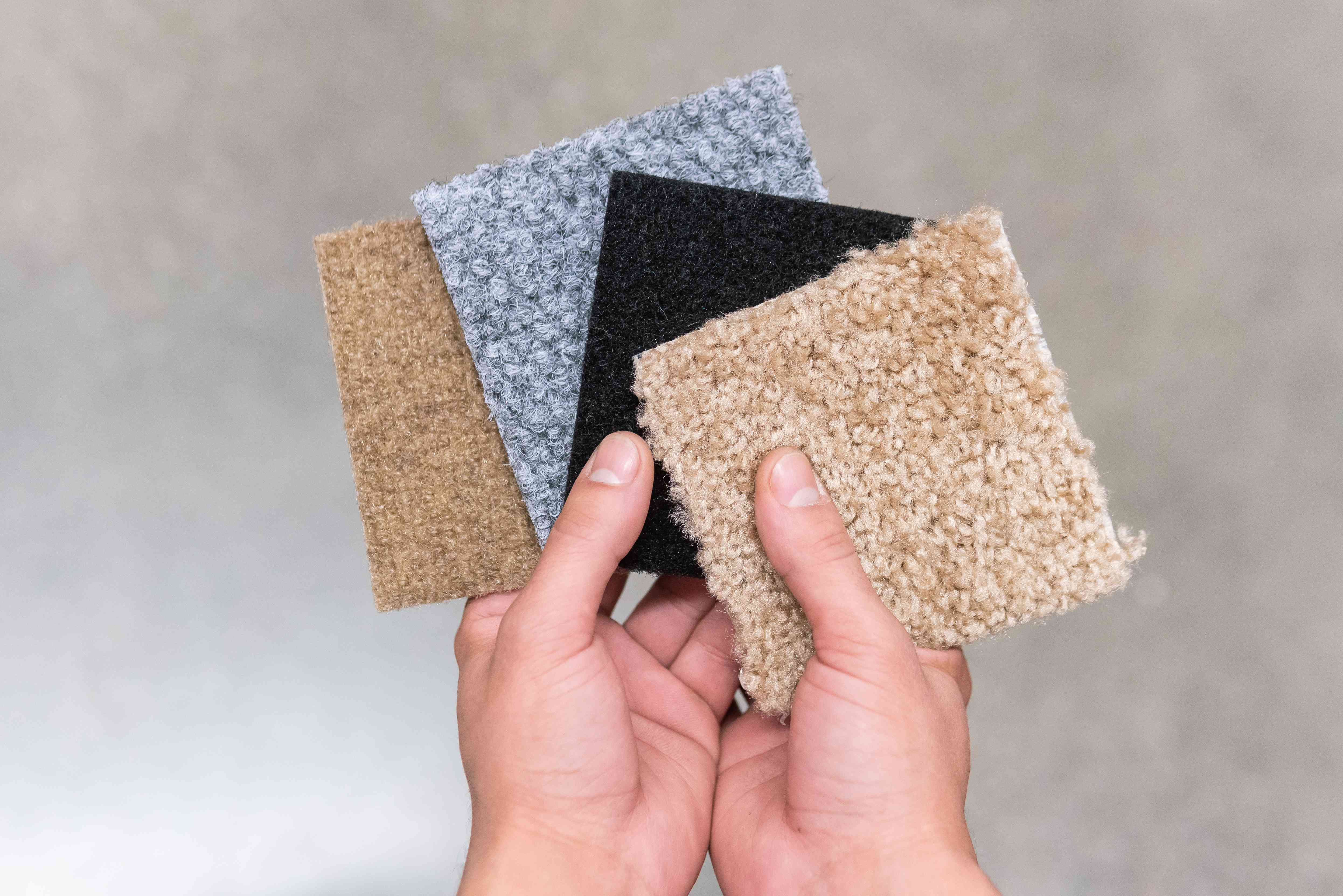 person holding carpet swatches