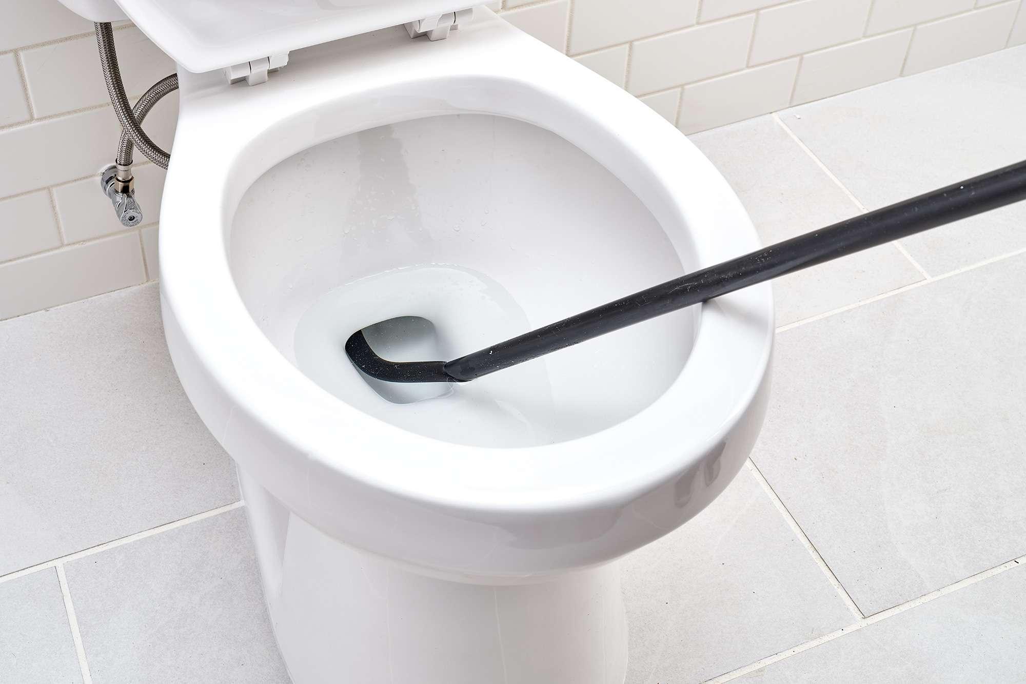Black toilet auger inserted inside hole of toilet bowl