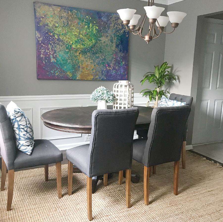 Dining room with gray walls, white wain scoting, and large picture on wall.