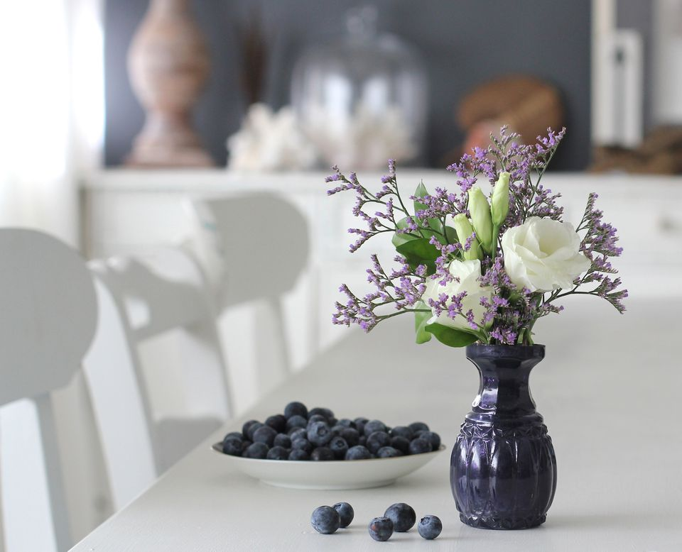 Blue flower vase with white and purple flowers next to a bowl of blueberries.