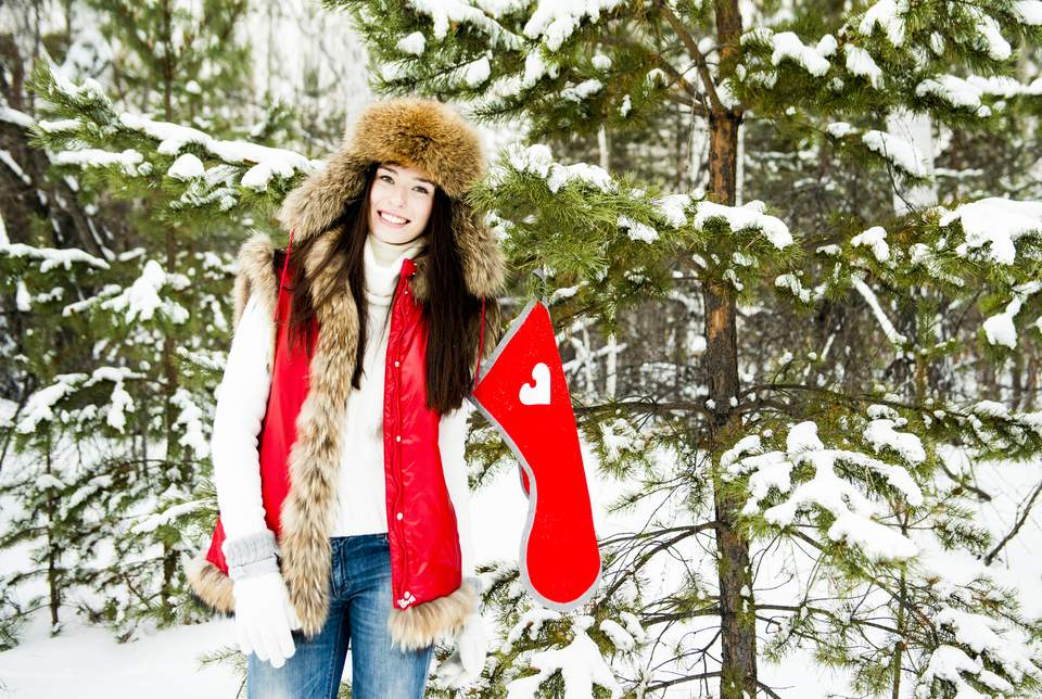 Caucasian girl hanging Christmas stocking on snowy tree