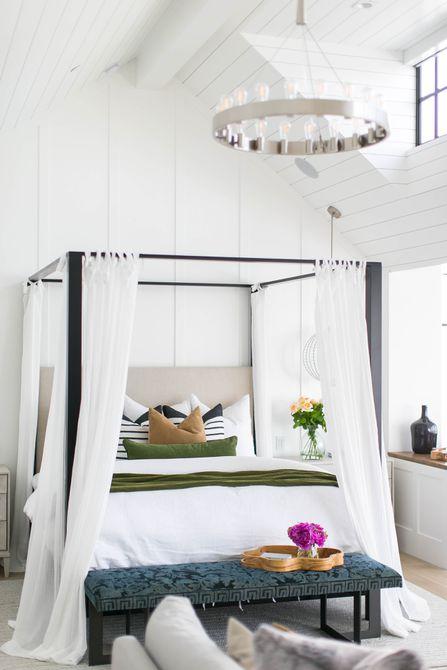 cama con dosel blanco y luminoso con cortinas blancas
