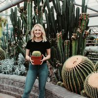 Cori is wearing a black shirt and jeans, holding a large cactus, and smiling in front of large cacti behind her.