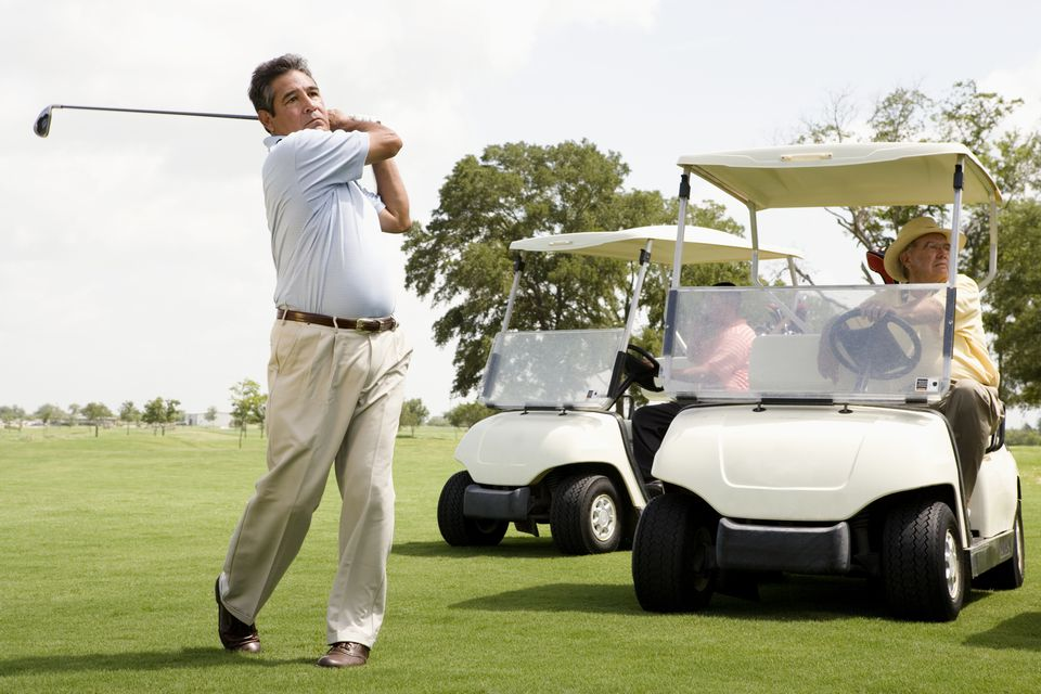 Man swinging golf club with two golf carts nearby