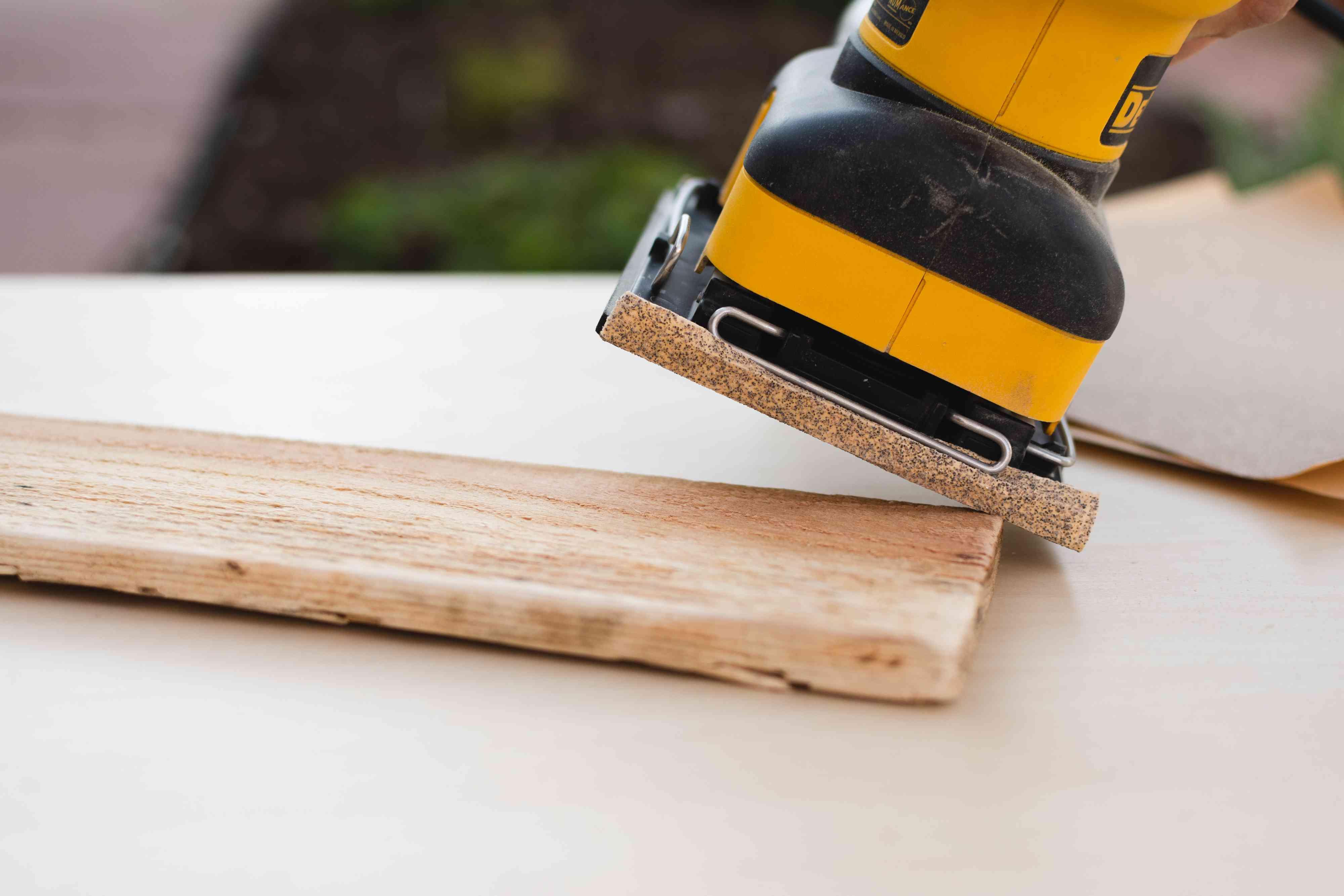 Sander rounding off edge of wooden plank