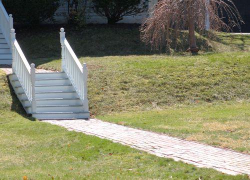 Foto de una pasarela de ladrillo que sube por una colina, puntuada por escalones.