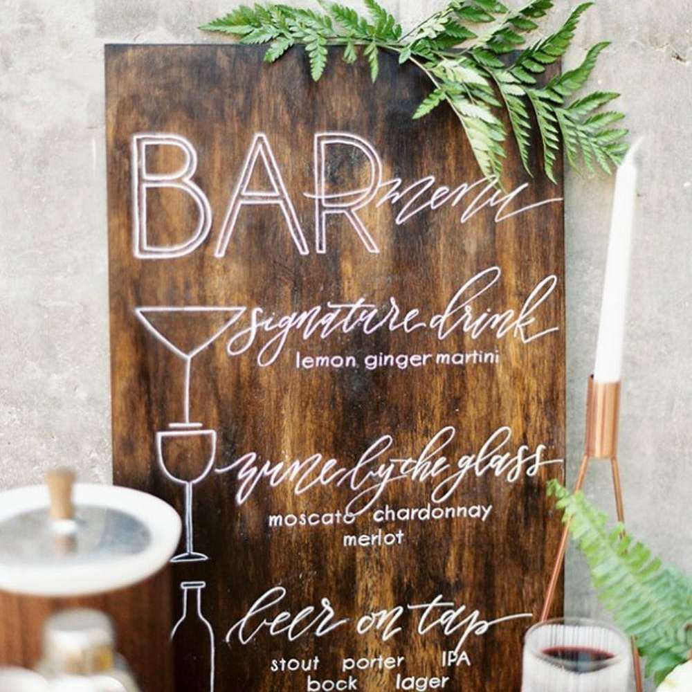 wooden sign for a bar at a wedding