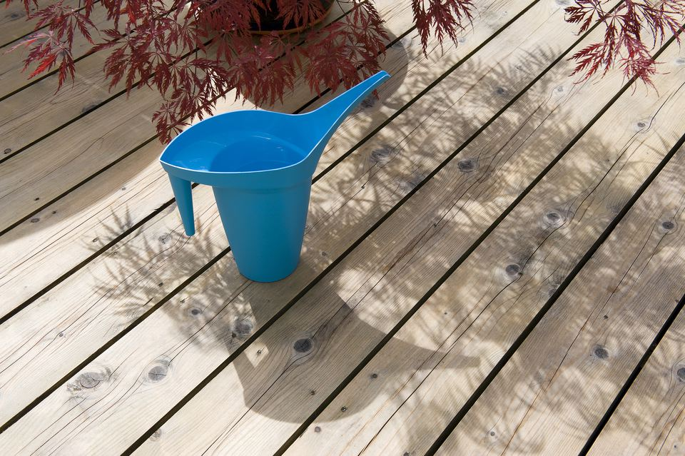 Blue watering can on wood timber decking