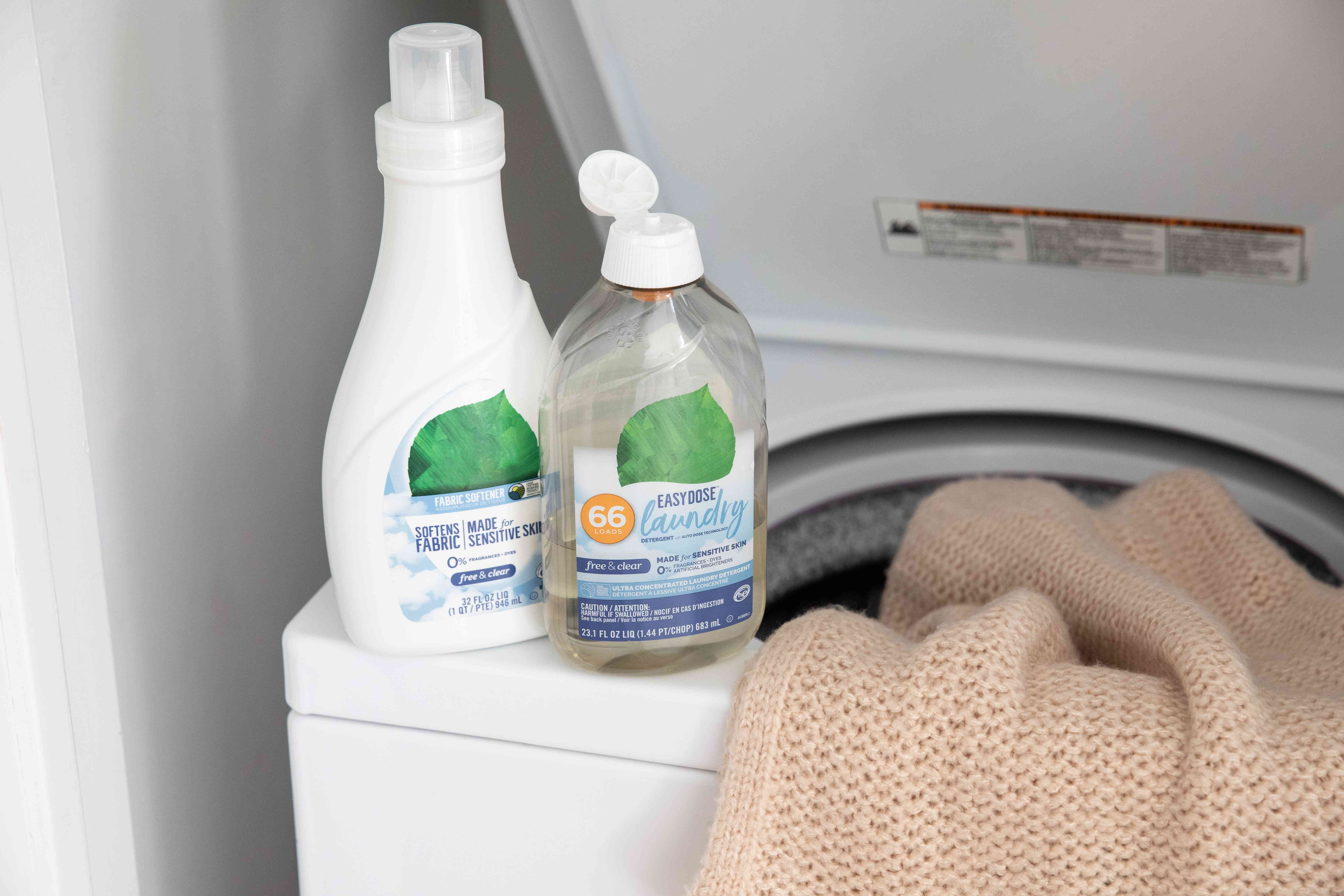 Laundry detergent bottles resting on open washing machine with acrylic sweater