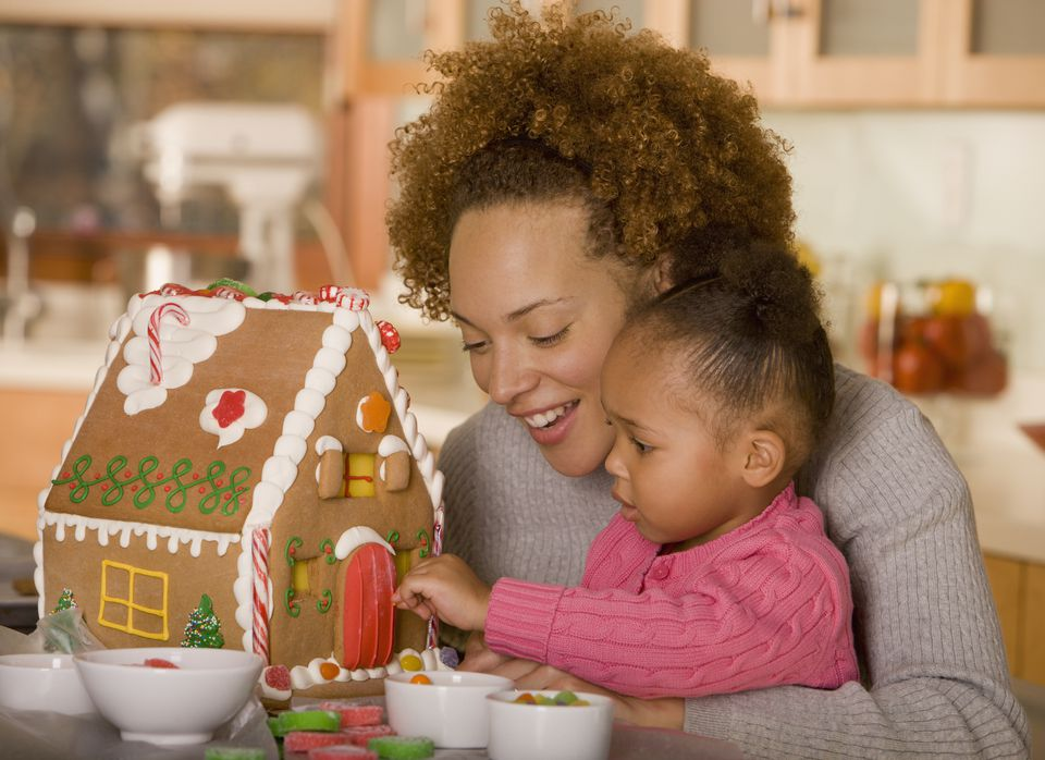 African mother and daughter making gingerbread house