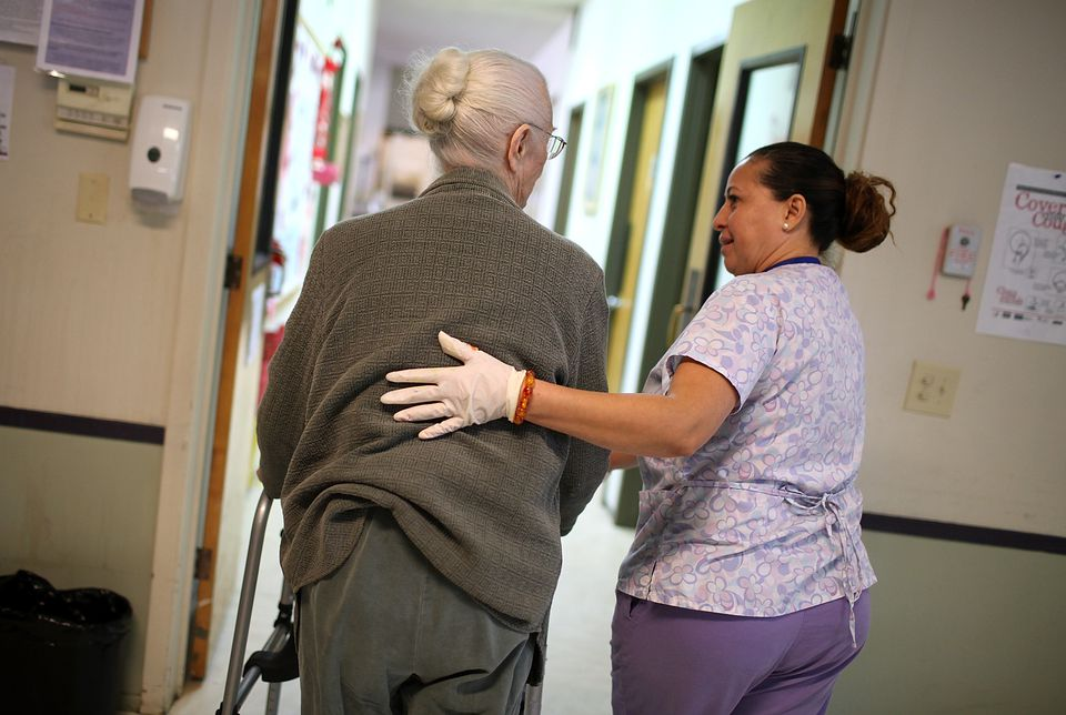 Woman in purple scrubs helping a patient.