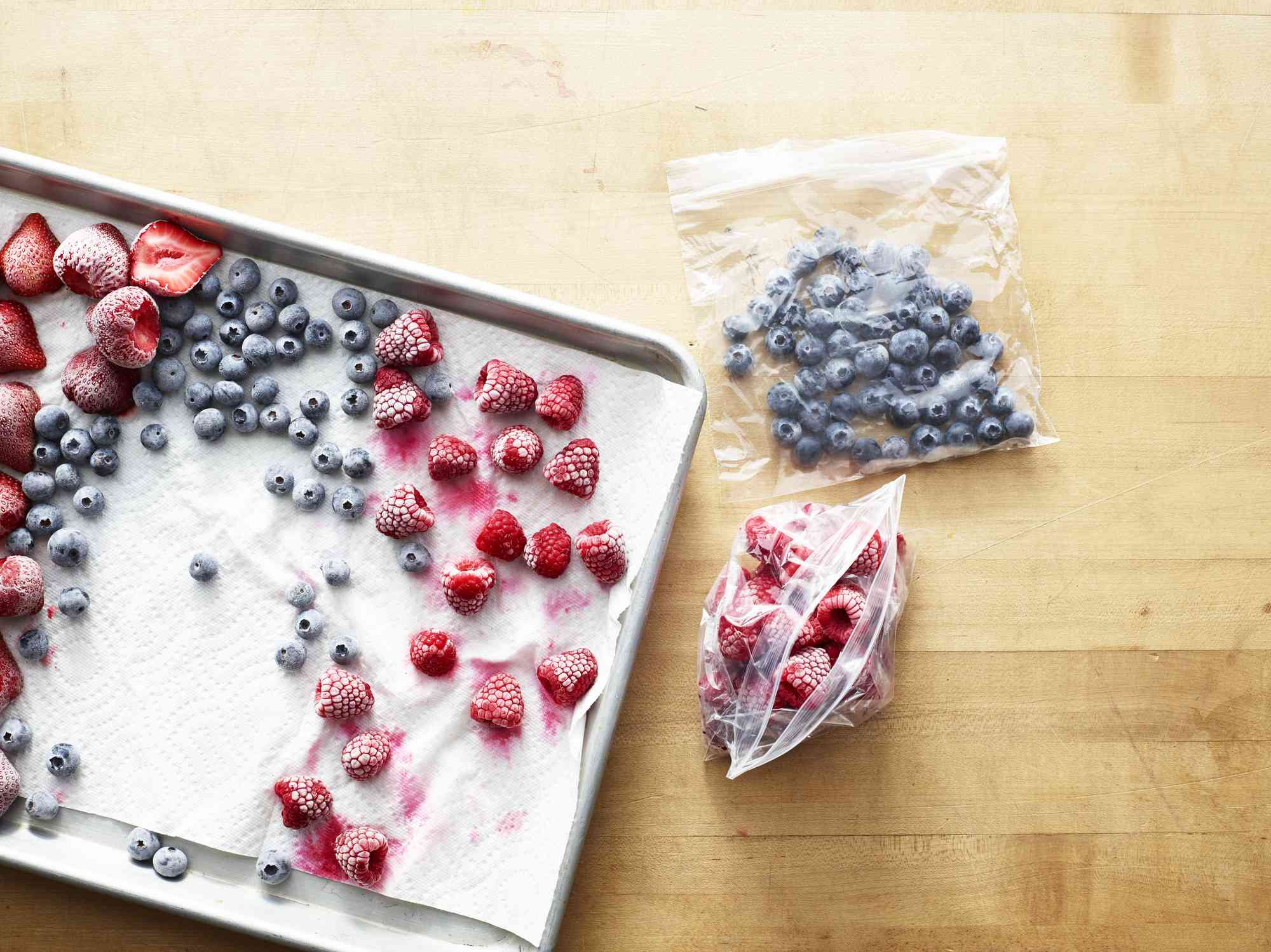Frozen berries on baking sheet and in plastic bags