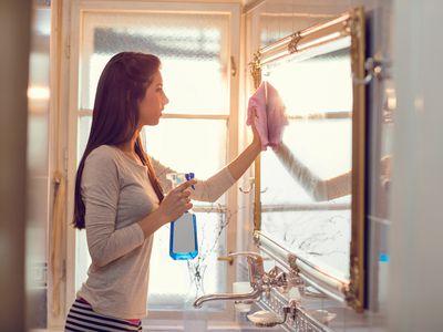 Woman cleaning bathroom mirror