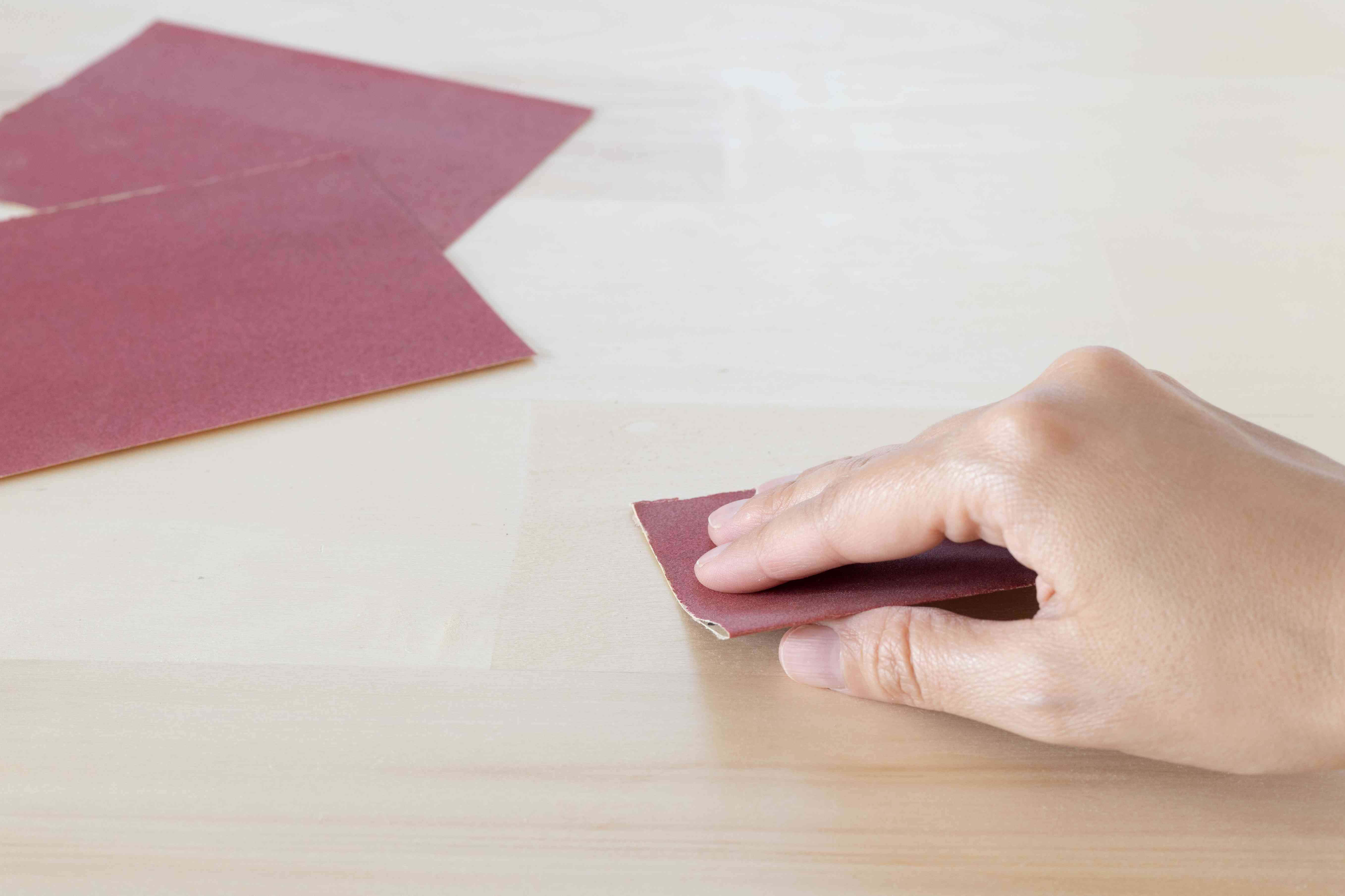 Red sandpaper rubbing wooden surface with super glue by hand