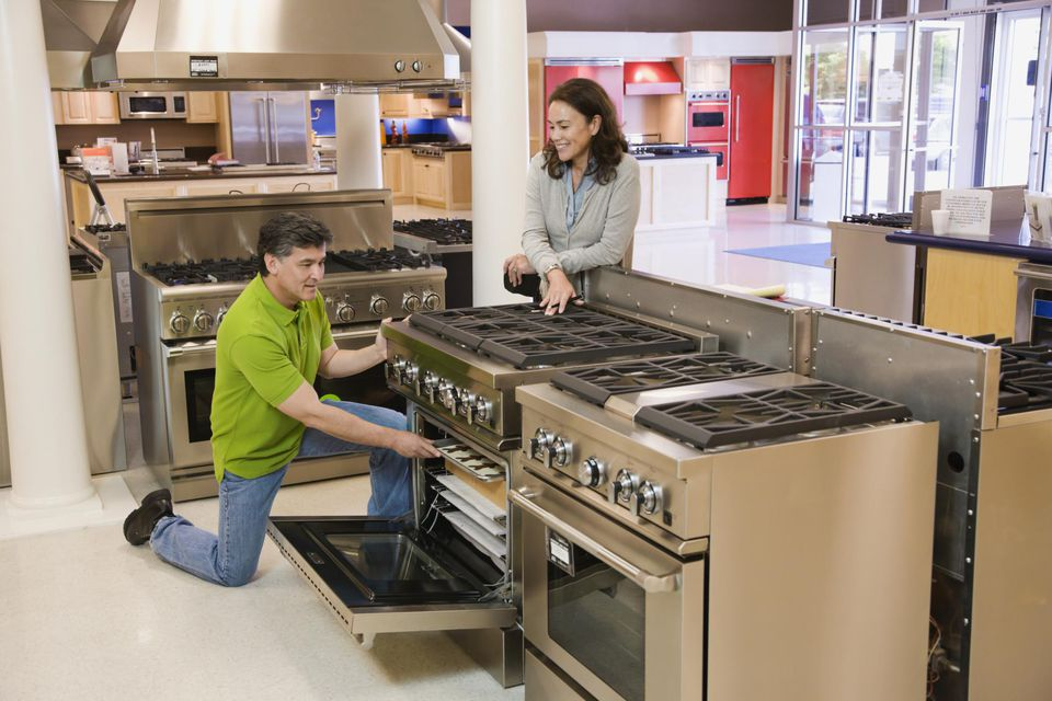 Two people examining an oven in a shop