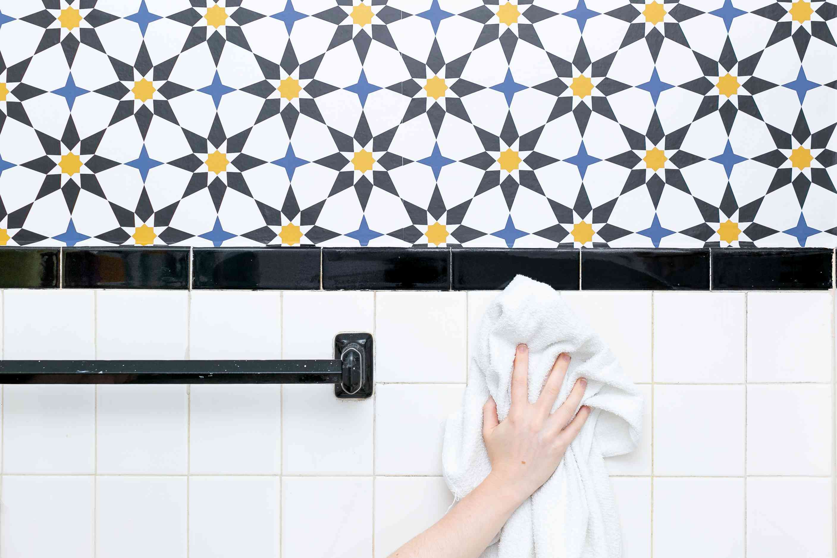 using a towel to dry the tiles