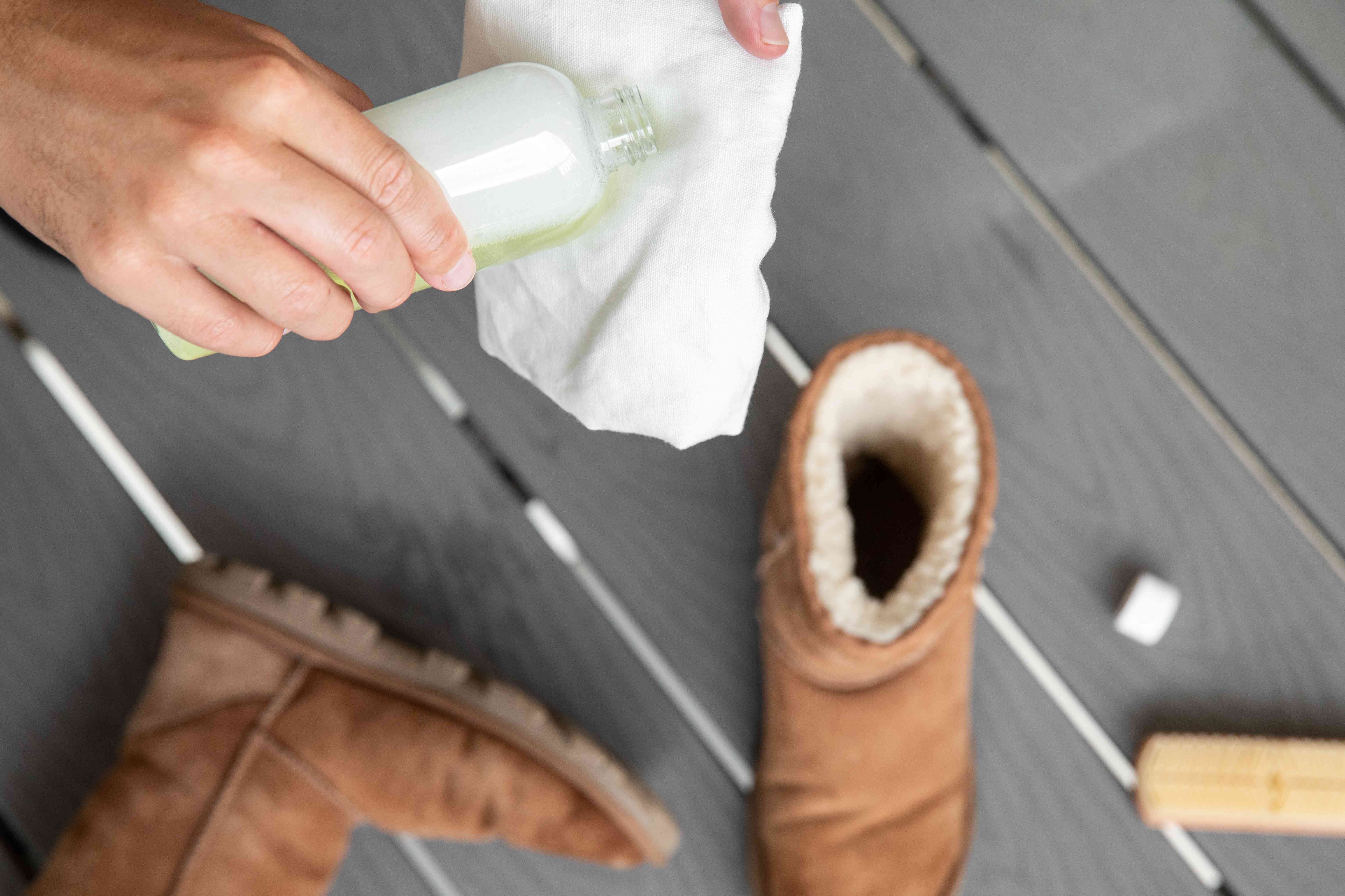 Someone applying suede cleaner to a white cloth