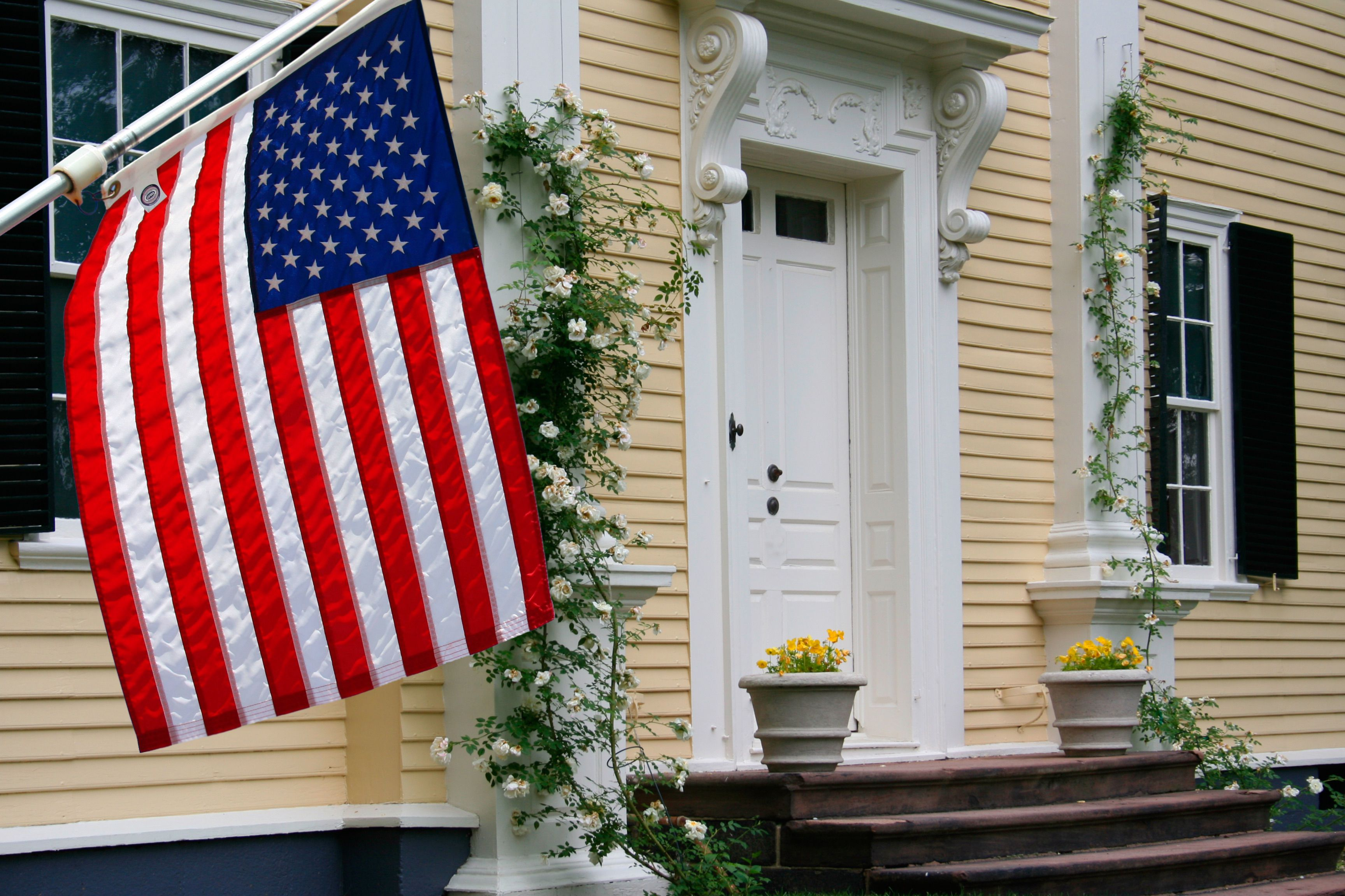 American Flag Hangs From the Clapboard Siding on a Colonial Home in Boston, Massachusetts