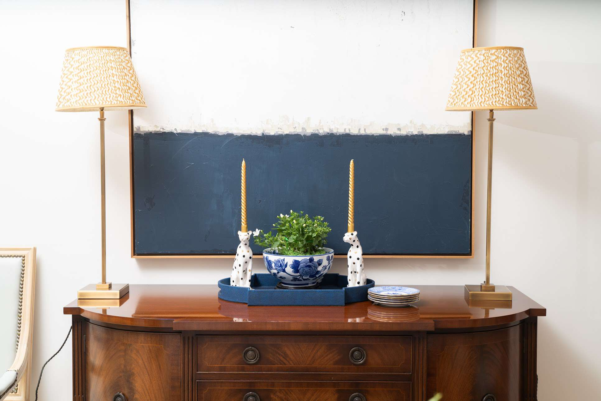 wooden sideboard with blue and white ceramics and patterned lamps on top