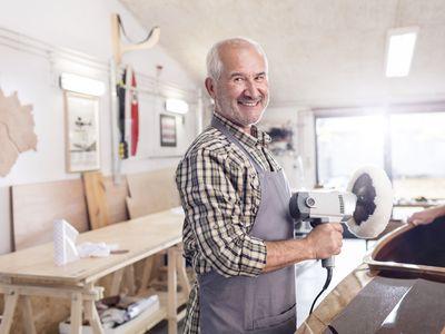 Portrait smiling, confident senior male carpenter using a buffer sander on wood boat in workshop