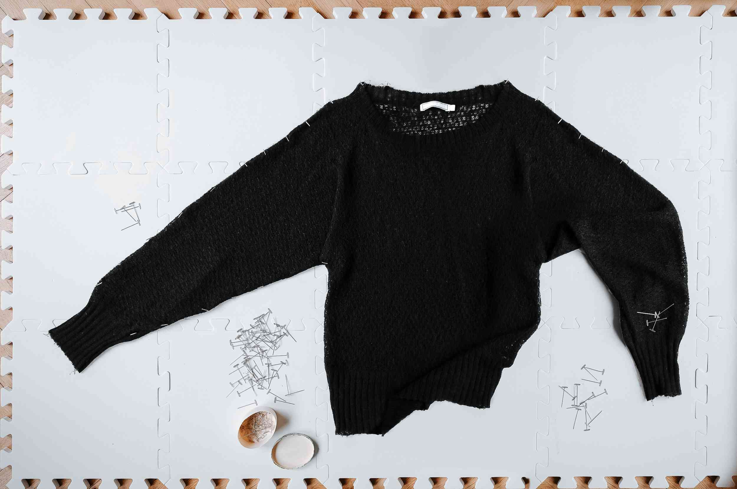 A black sweater pinned to a board to dry