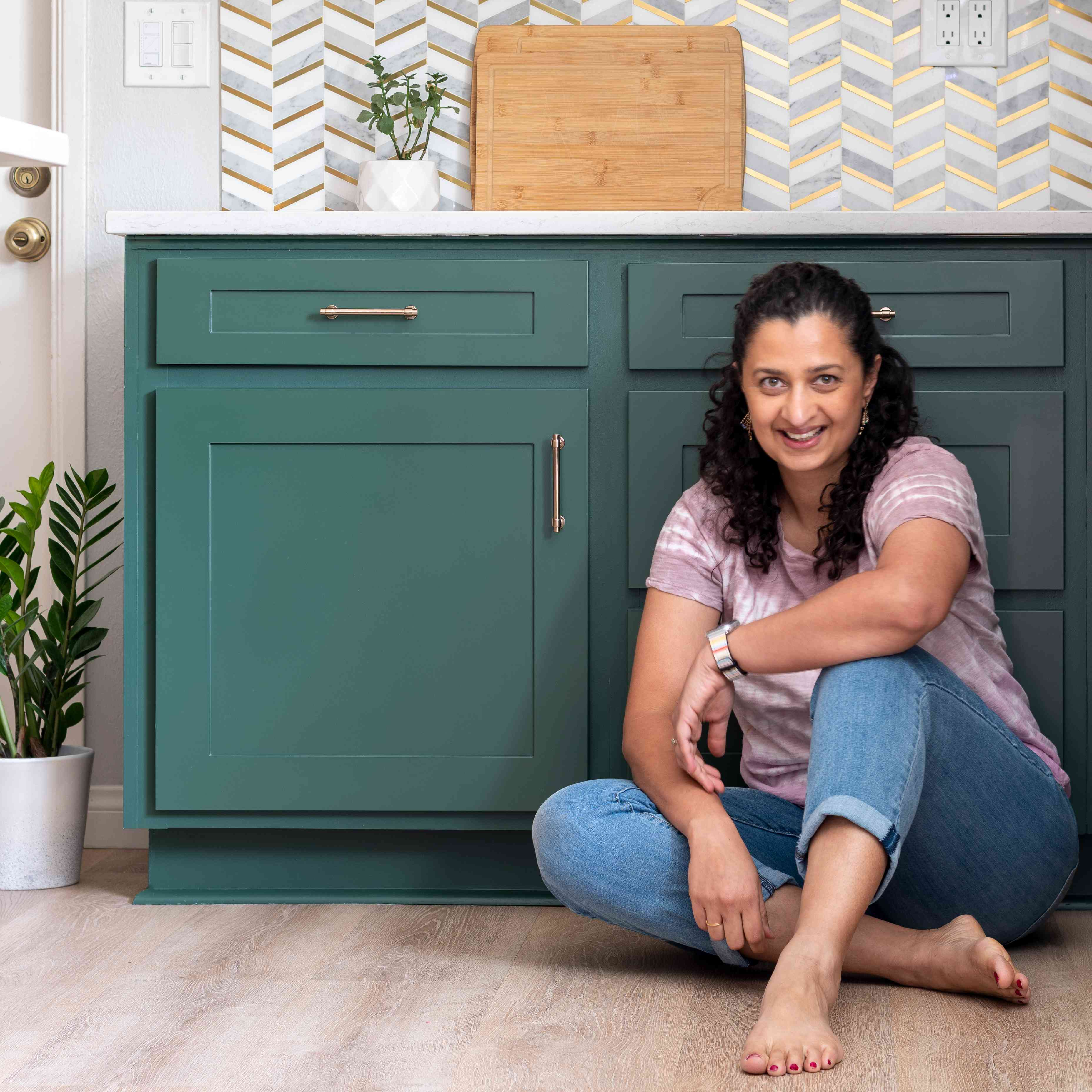 Anika Gandhi sitting in front of a kitchen cabinet
