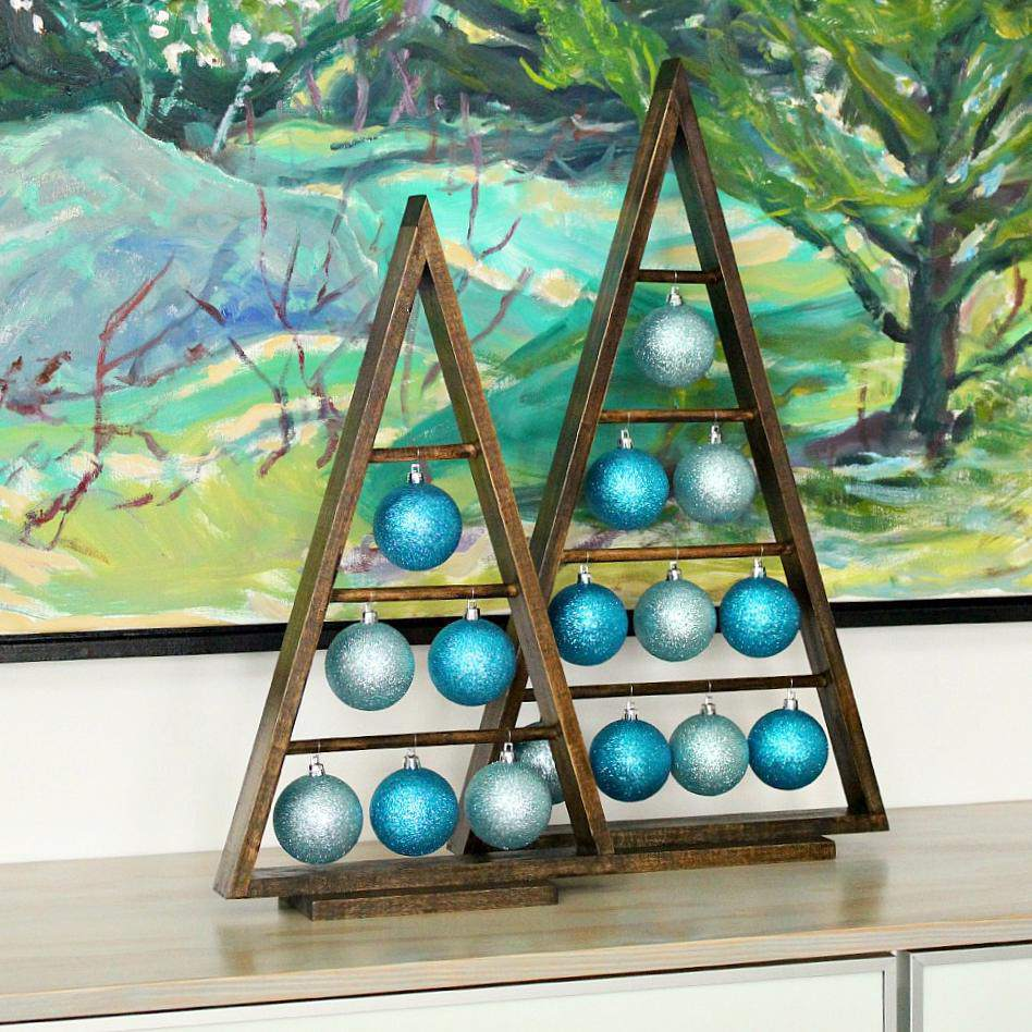 Christmas ornaments hanging from wooden a-frames