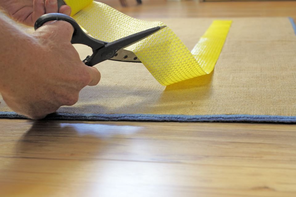 Male hand cutting rug grip tape applied to back of area rug
