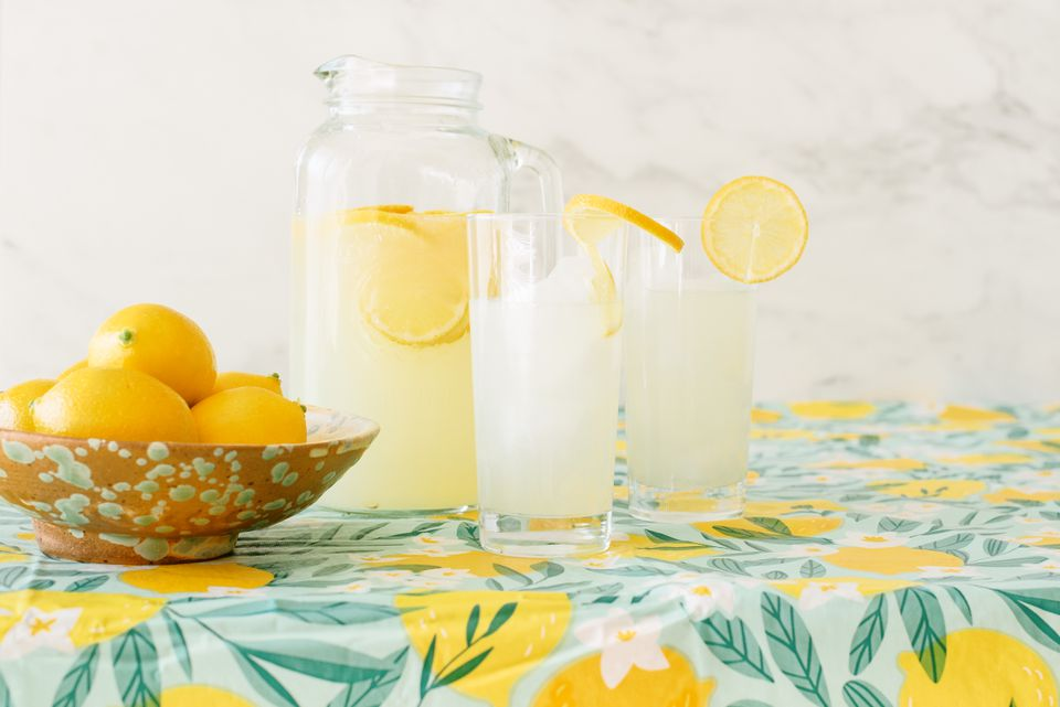 Vinyl tablecloth with illustrated lemons and foliage with bowl of lemons and glass pitcher and drinking glasses with lemonade