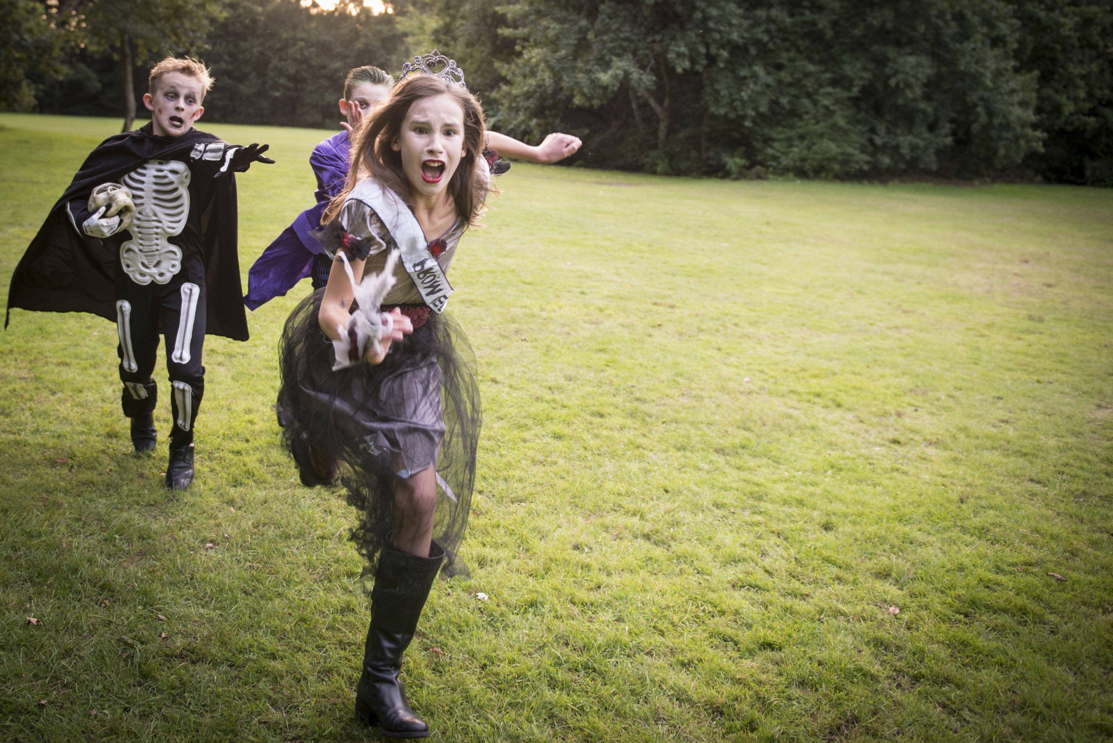 children in Halloween costumes running