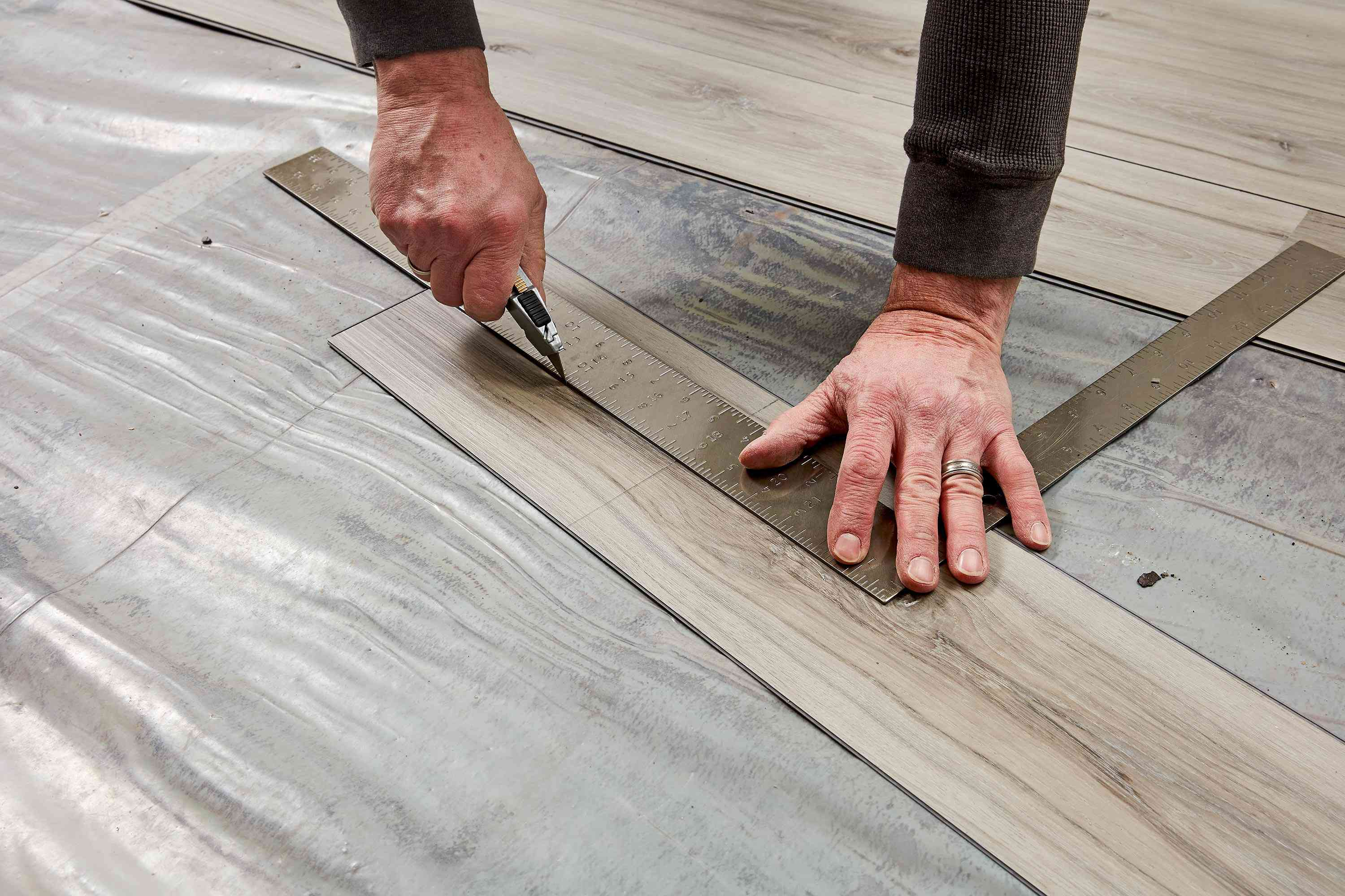 Vinyl plank measured and cut by utility knife