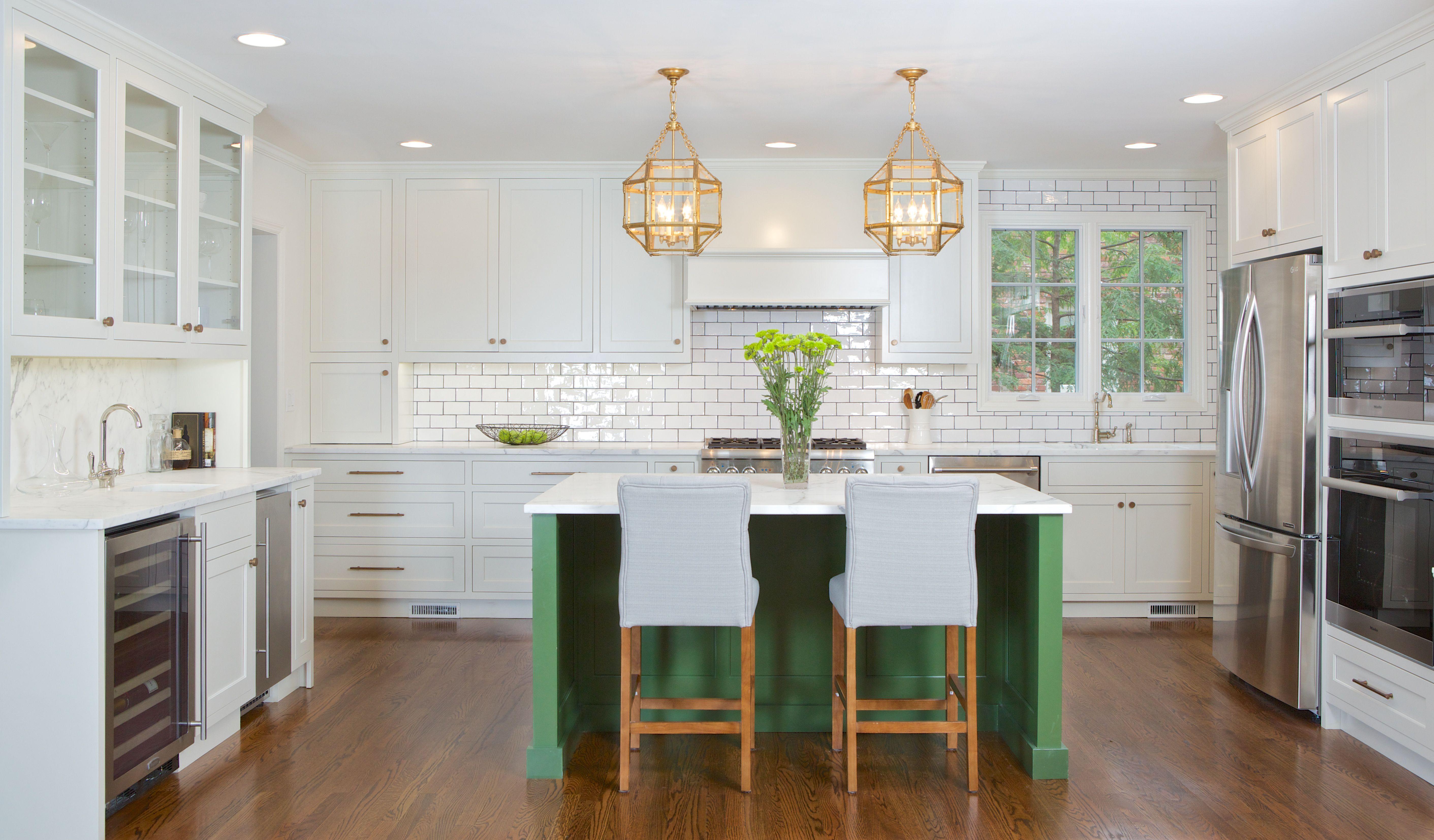 Cocina verde y blanca de Apple con luces colgantes doradas