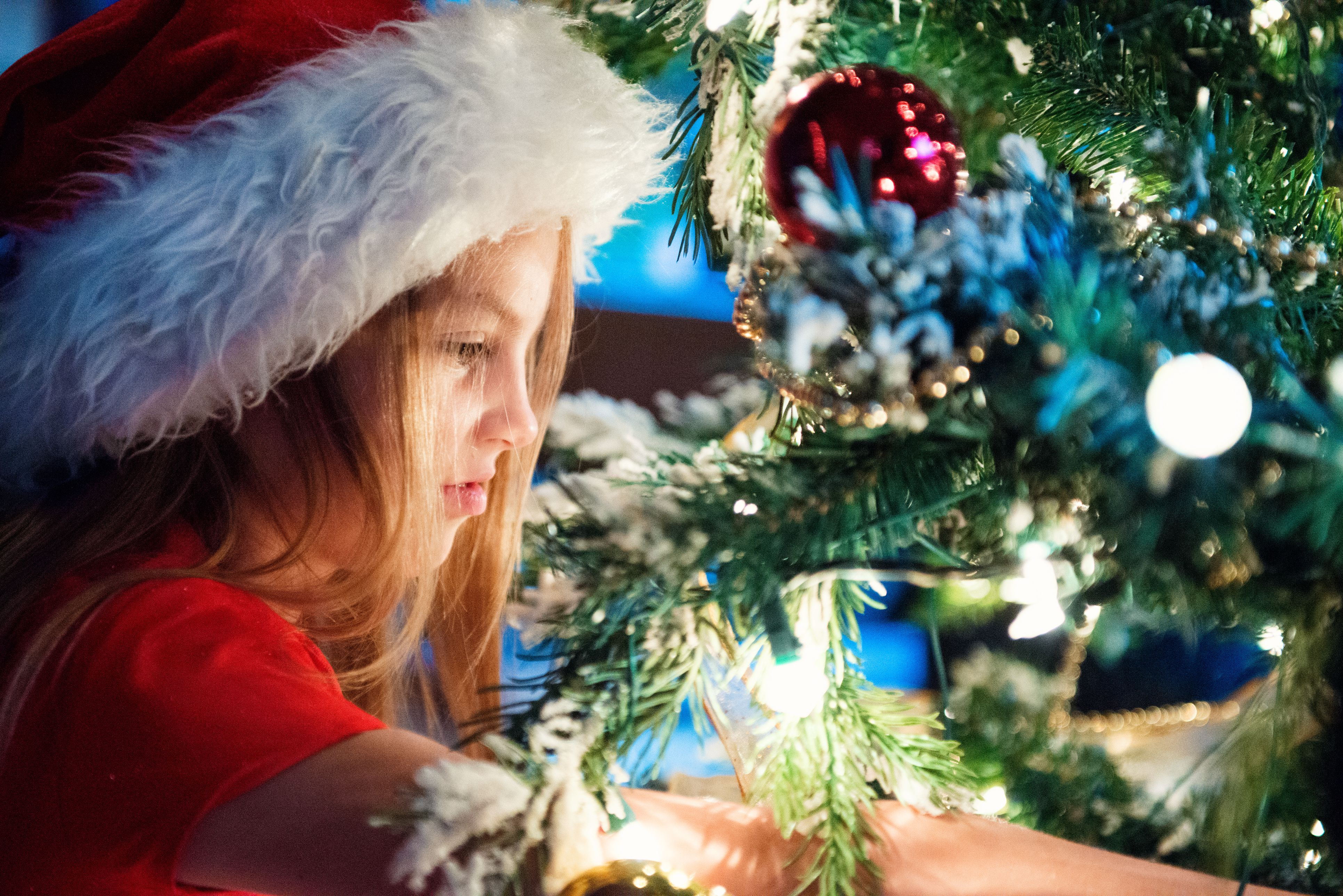 A little girl in a Santa hat by the Christmas tree