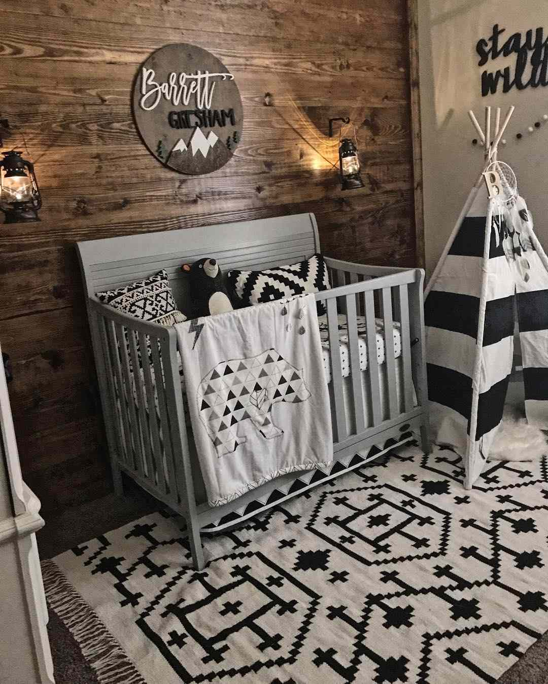 Woodland themed nursery with wood paneled accent wall