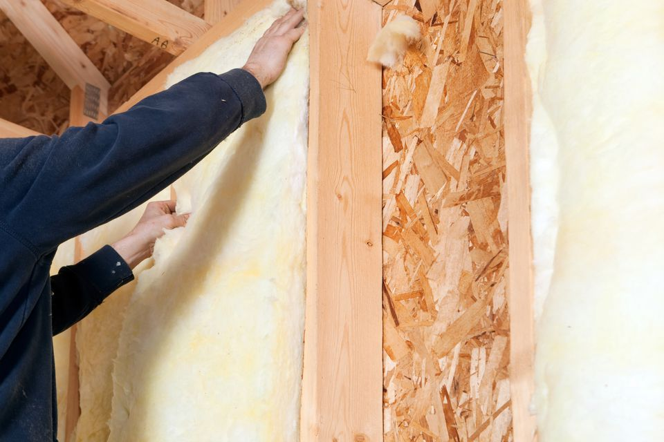 Worker Installing Fiberglass Batt Insulation between Wall Studs