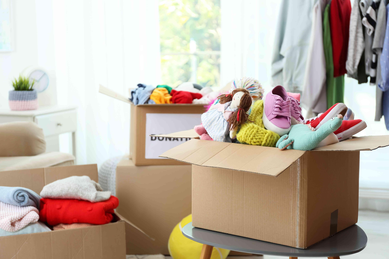 Caja de donación con ropa y juguetes en la mesa en el interior. Espacio para texto