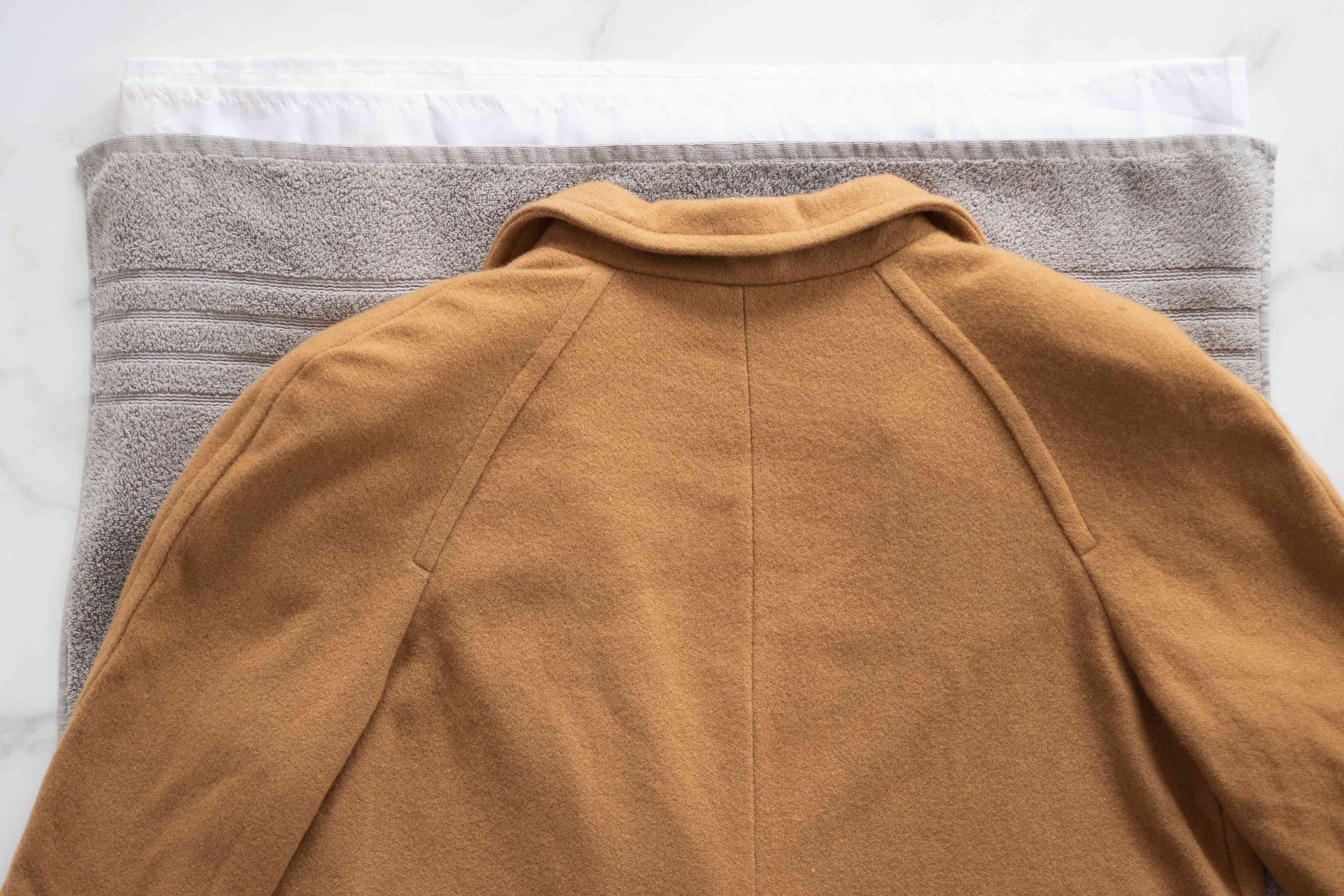 Tan wool coat layed flat on gray towel to air dry