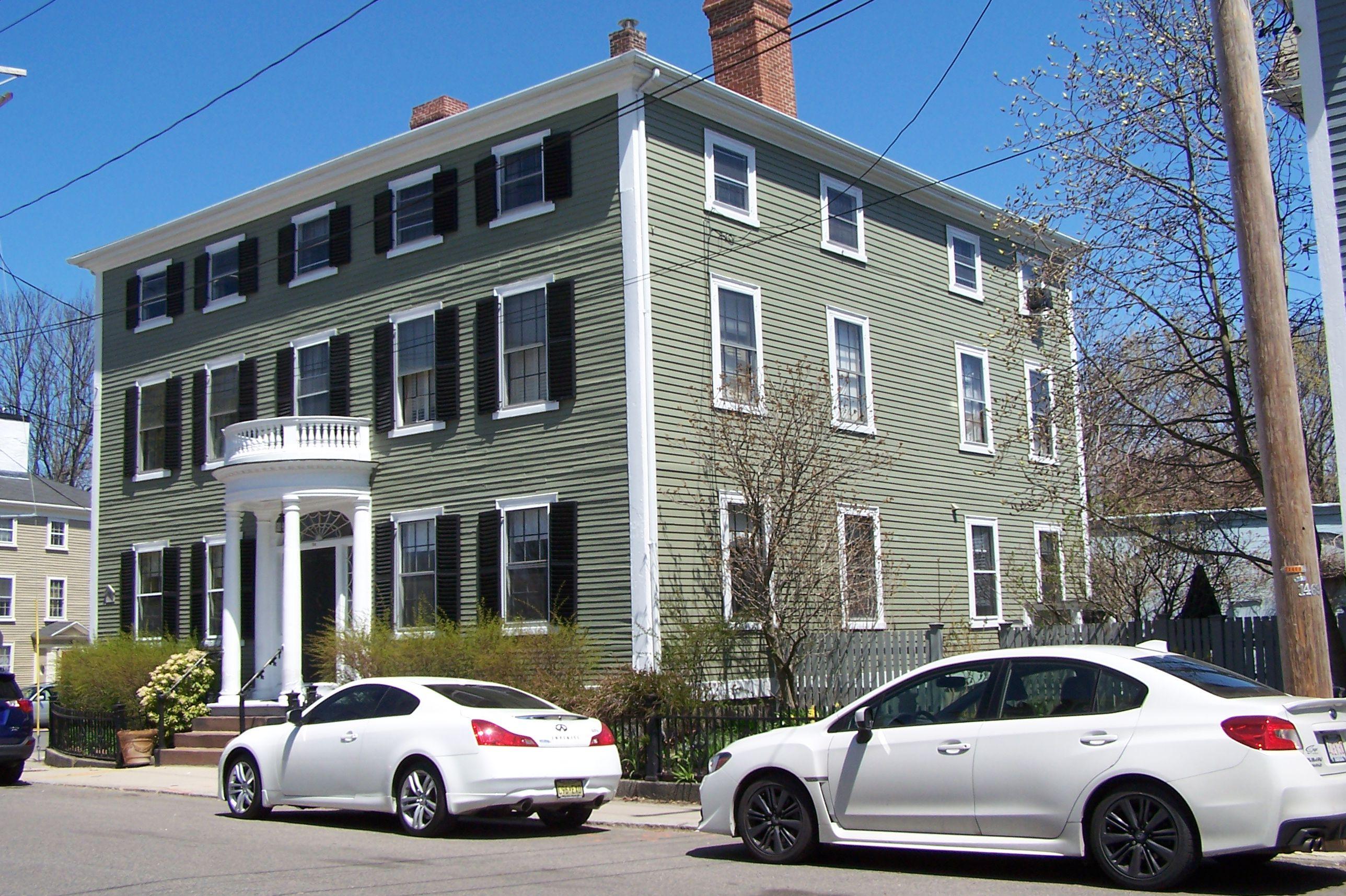 Gran casa colonial verde de 2 1/2 pisos en New Inglaterra, con techo plano, pórtico de entrada de un piso y persianas delanteras pero no laterales entrada frontal con ventanas y puertas arqueadas