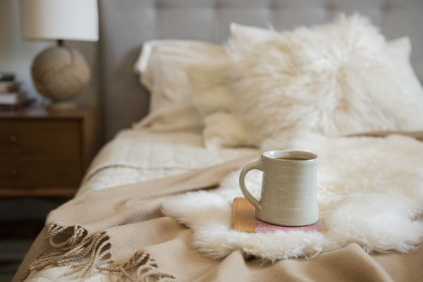 Cozy bed with luxurious throw blankets and a coffee cub on top of a book.