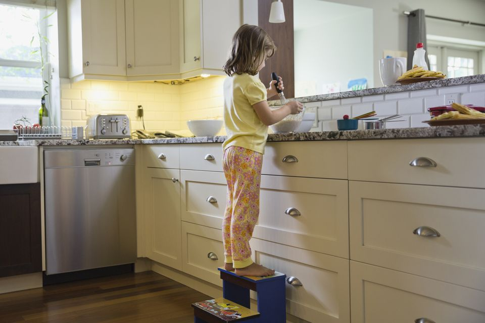 Little girl on a wooden step stool