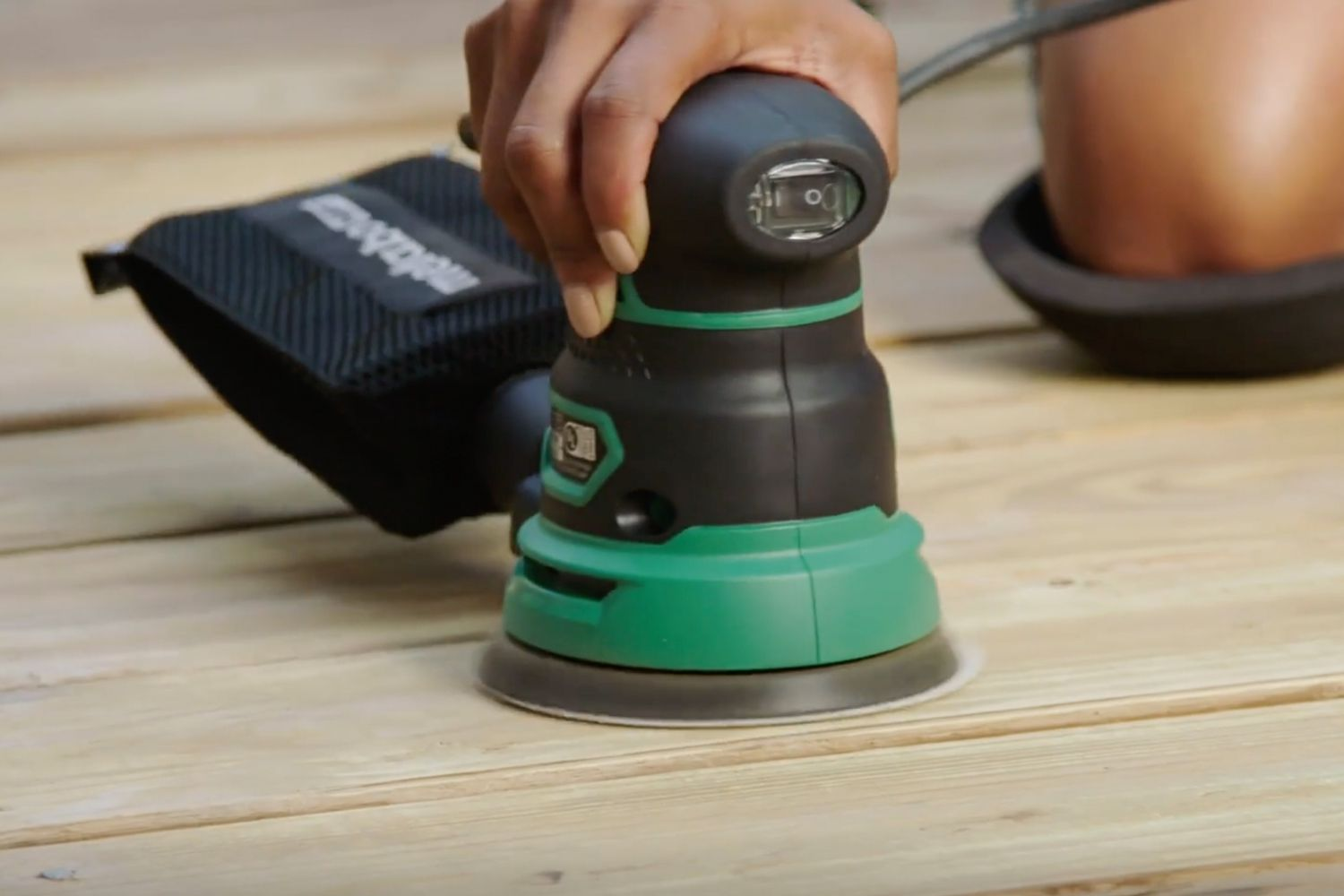 person sanding a wood deck