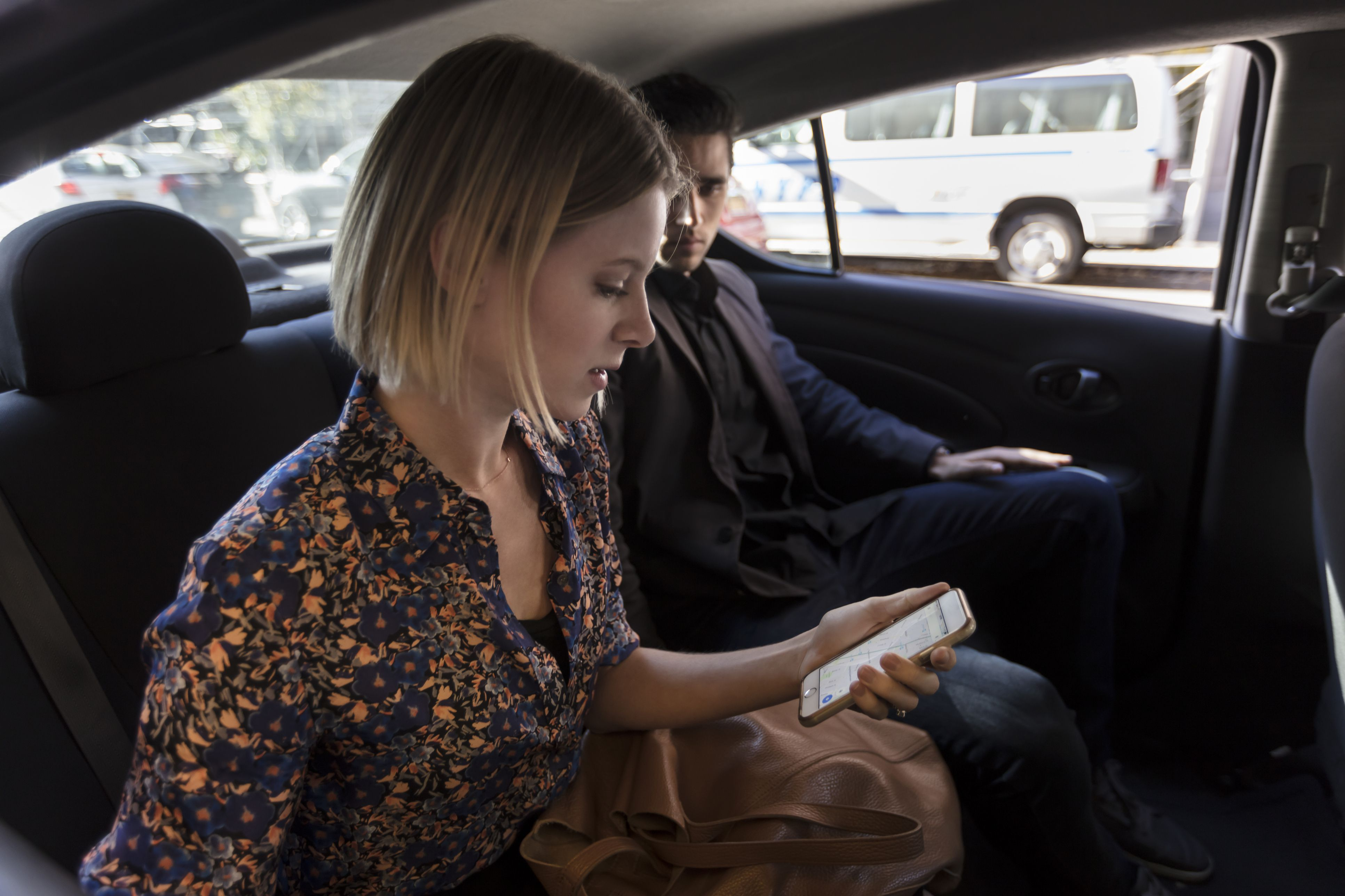 Man and woman sitting in car looking at phone