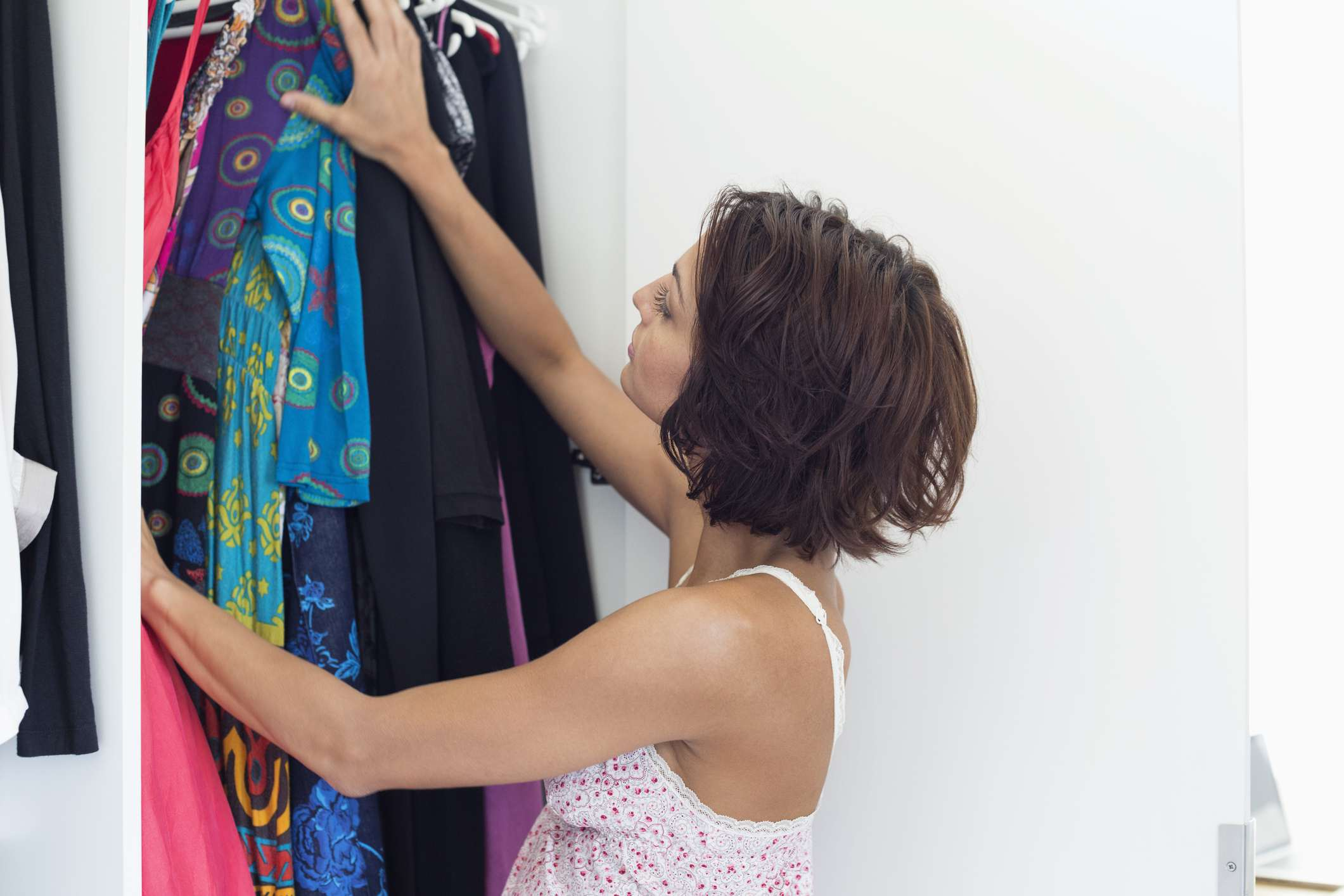 Woman looking at clothes hanging in a closet.