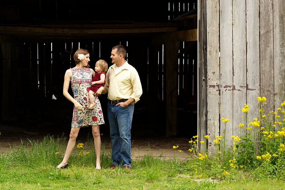 Modern mother, father and adopted baby girl standing in front of a barn.