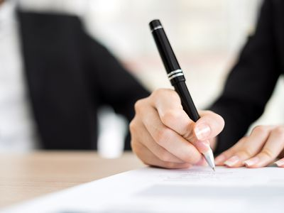 A person in an office writing on a piece of paper with a black pen.