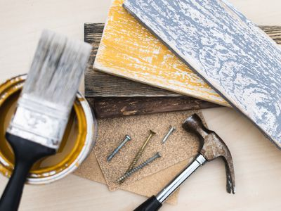 Blue and yellow distressed wood planks on wooden block next to hammer, nails, paint brush and bucket of paint stain