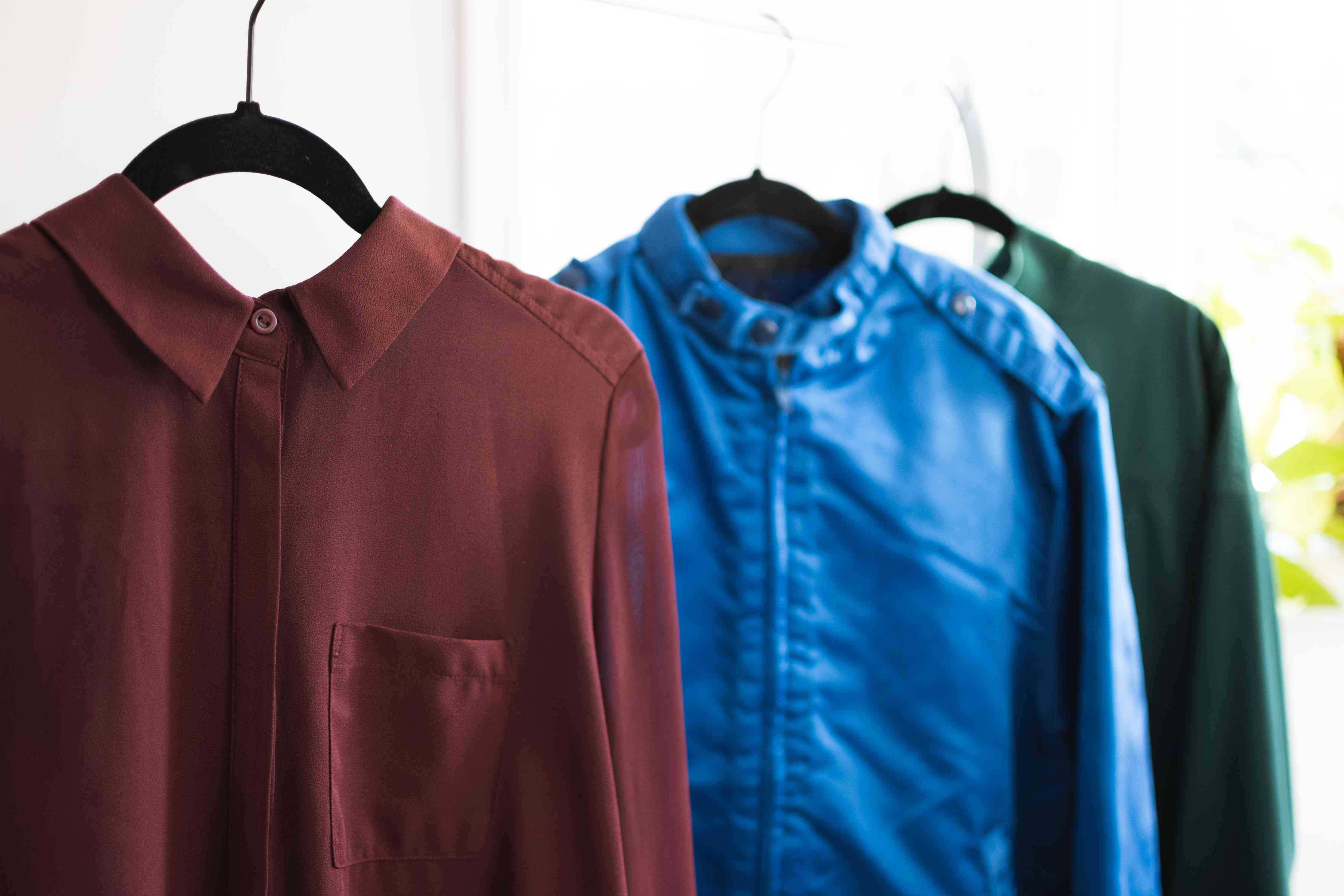 Red, blue and green polyester shirts and jackets on black hangers