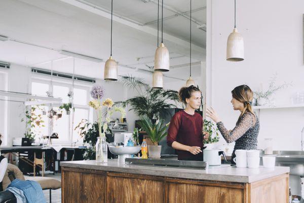 Creative businesswomen discussing at kitchen island in office