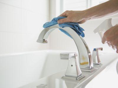 Woman polishing bathroom fixture with blue rag and spray.