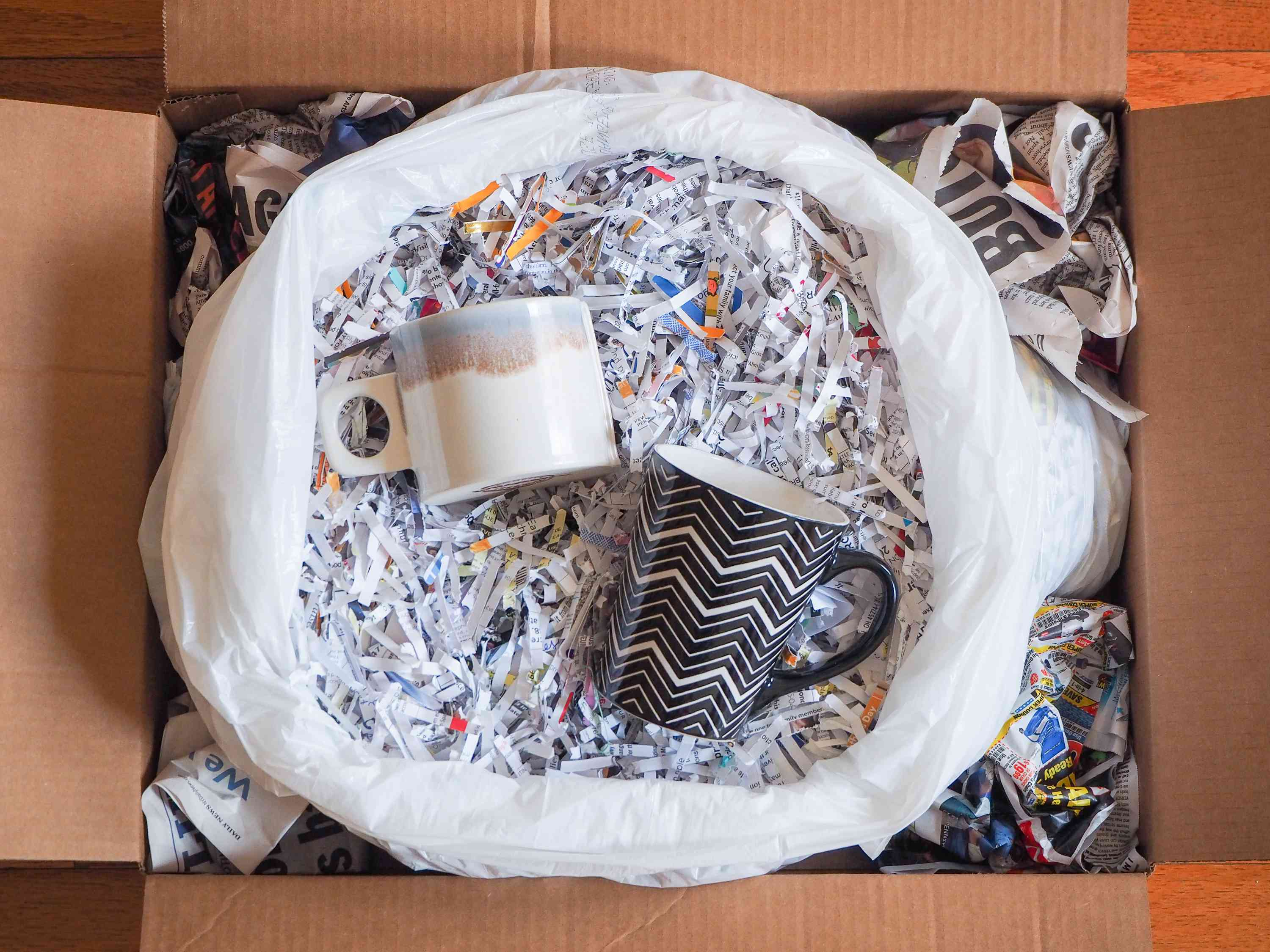 Moving box open with shredded and crunched paper to protect coffee cups